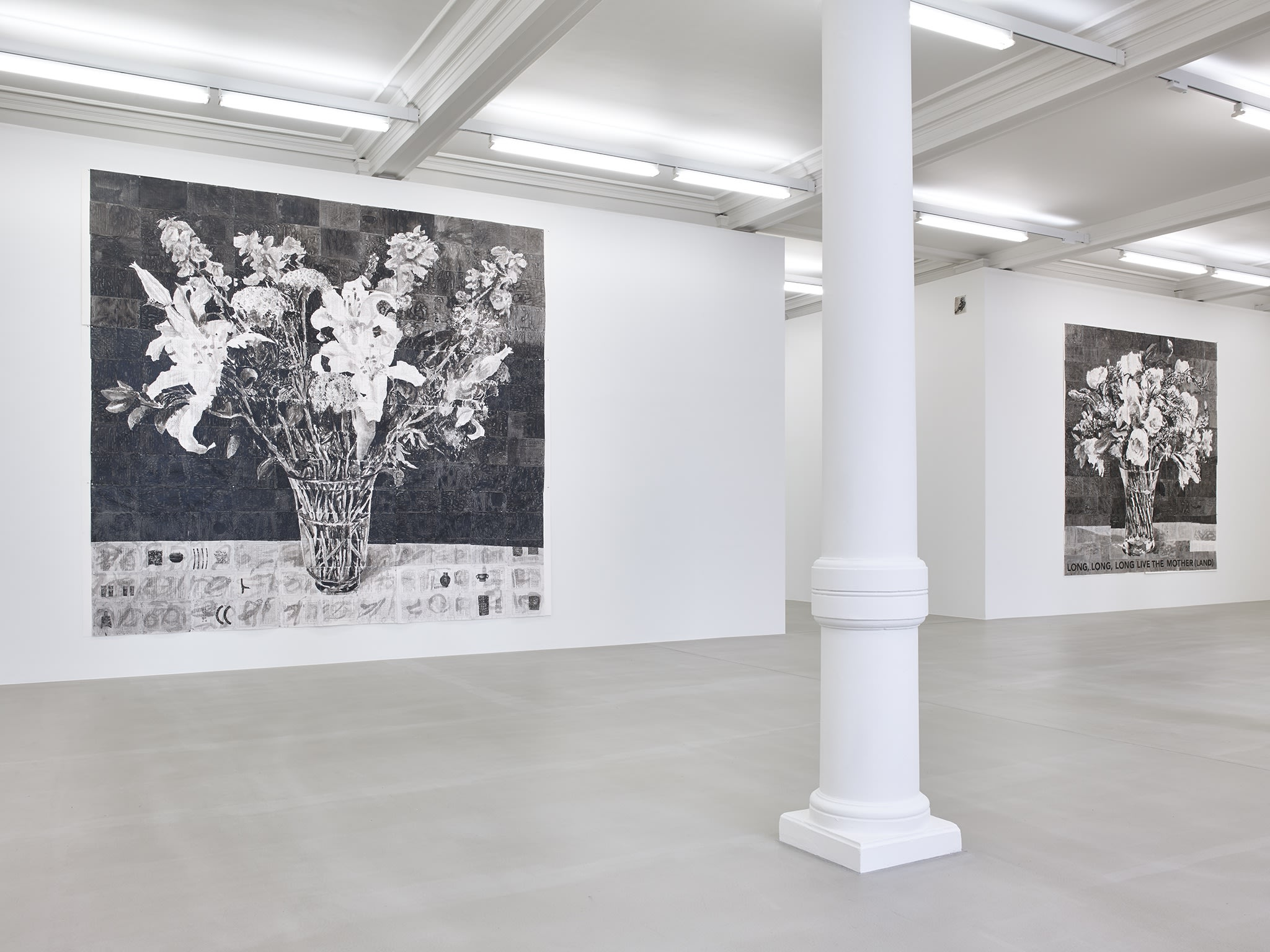 In a large white space with columns, two large black and white paintings of flowers in a pot hang on walls opposite sides of a hallway. One on the left reads, at the bottom: LONG, LONG, LONG, LIVE THE MOTHER(LAND)