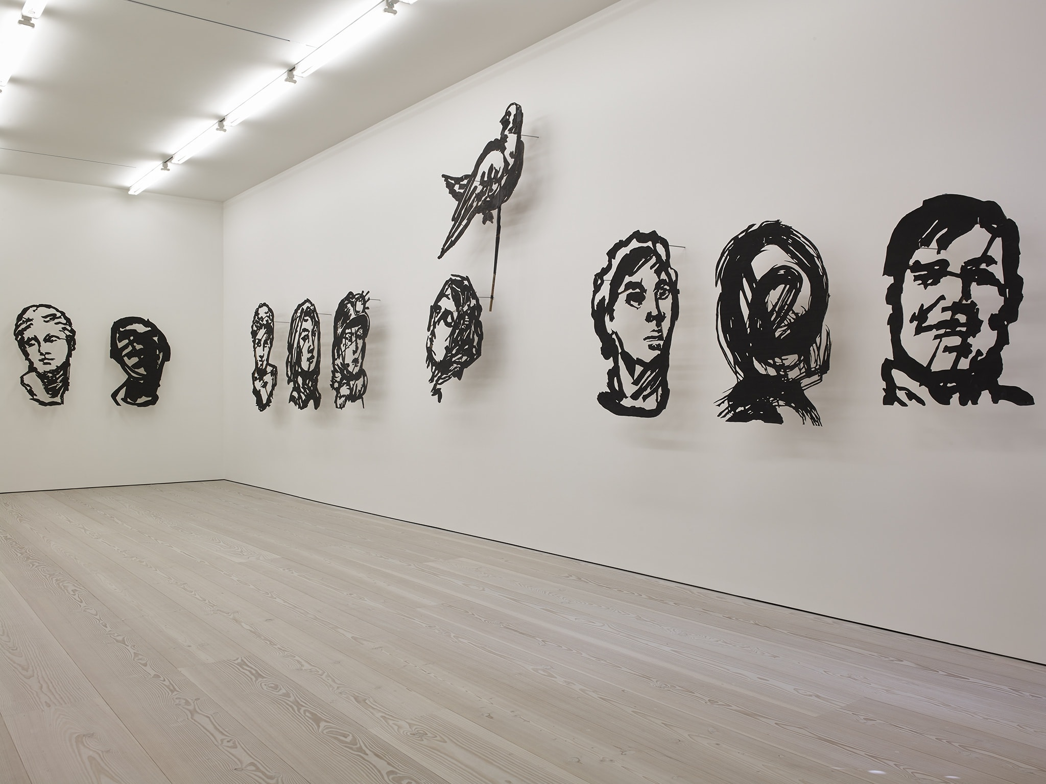 In a large white space, many sculptures of silhouettes of faces hang, made of black metal. They are made so only the features are represented, and the rest of the faces are filled out by the white wall they hang on.