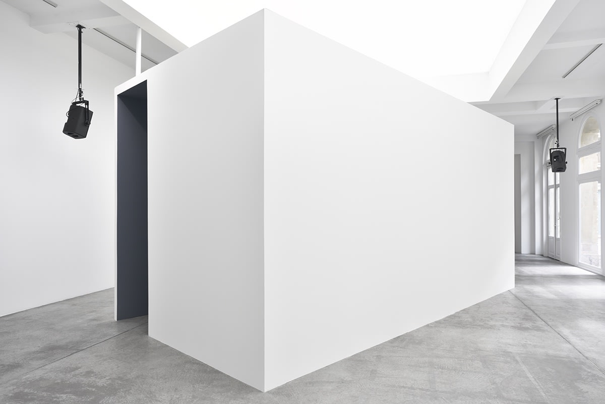 A screening room - which looks like a large white cube - sits in a white gallery space. The inside of the room cannot be seen. A couple of speakers hang over head, spread around the gallery.