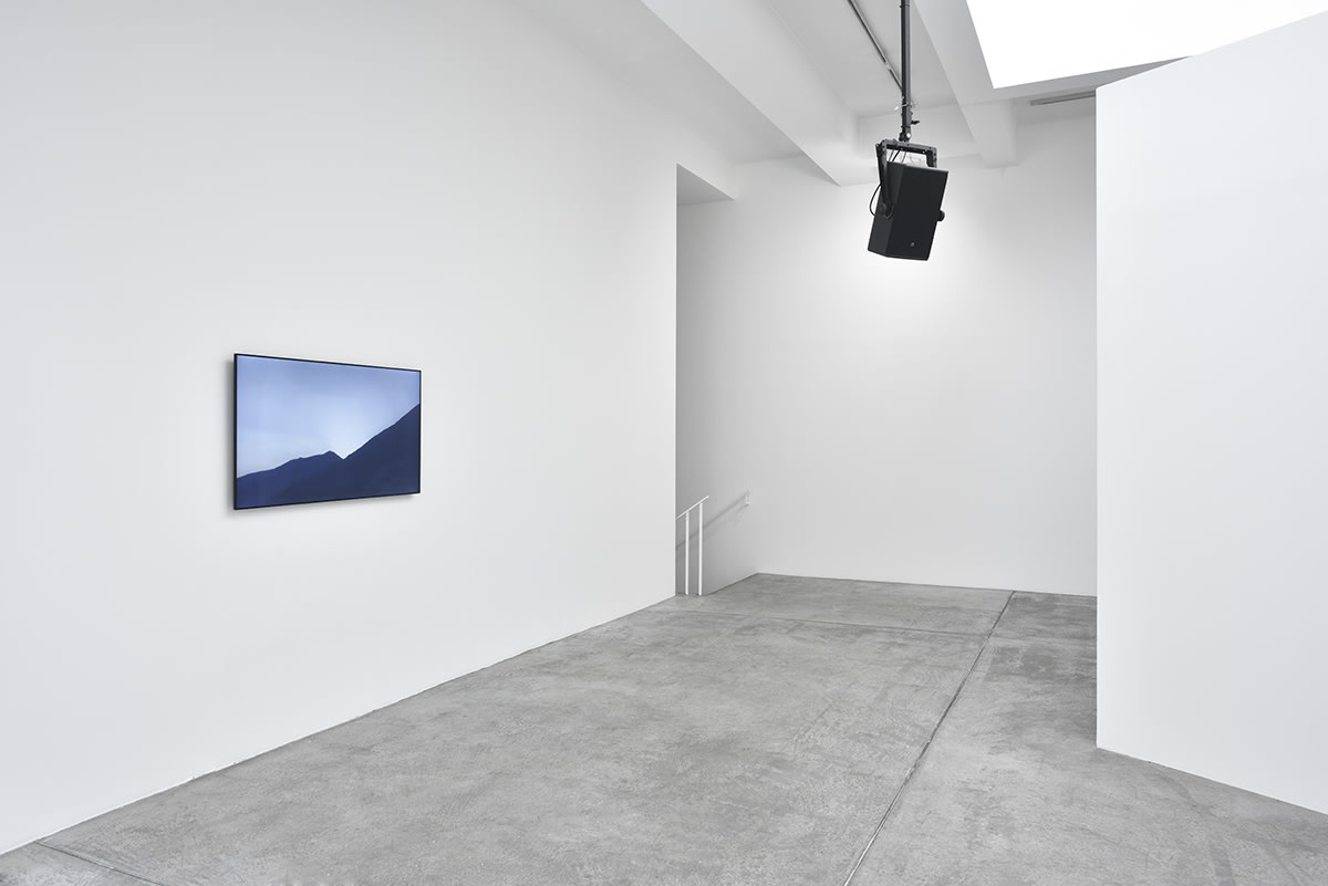 In a white gallery space, the photo of a sunrise over a mountain, all blue in tint, hangs on a wall. Hanging from the ceiling in front of it is a black speaker.