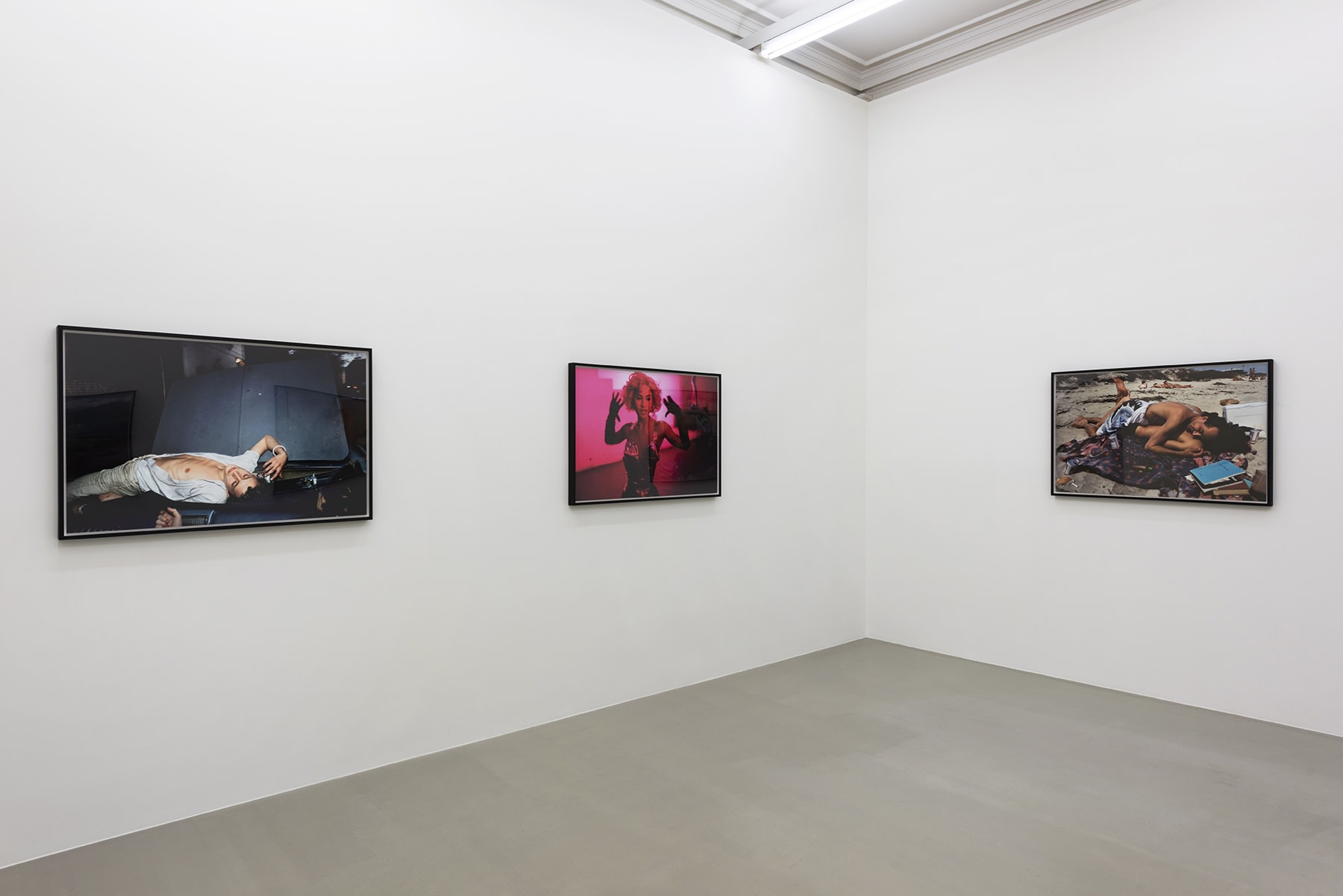 3 colorful photographs hang in a white gallery space.