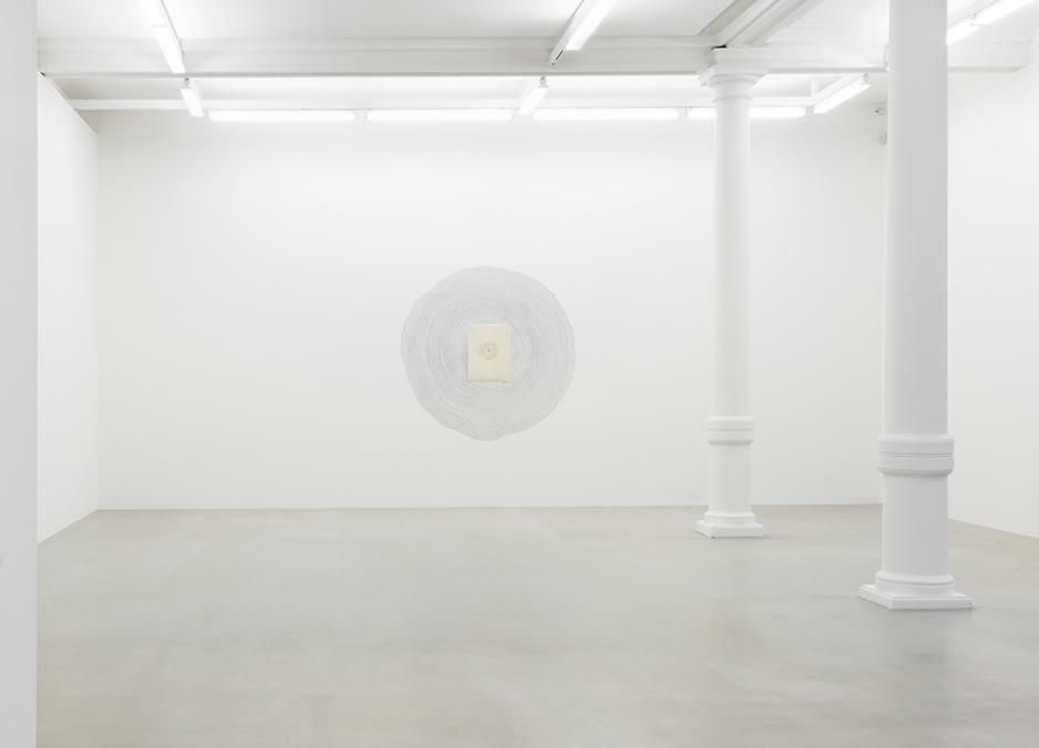 A circular form is drawn on the gallery wall next to 2 columns.