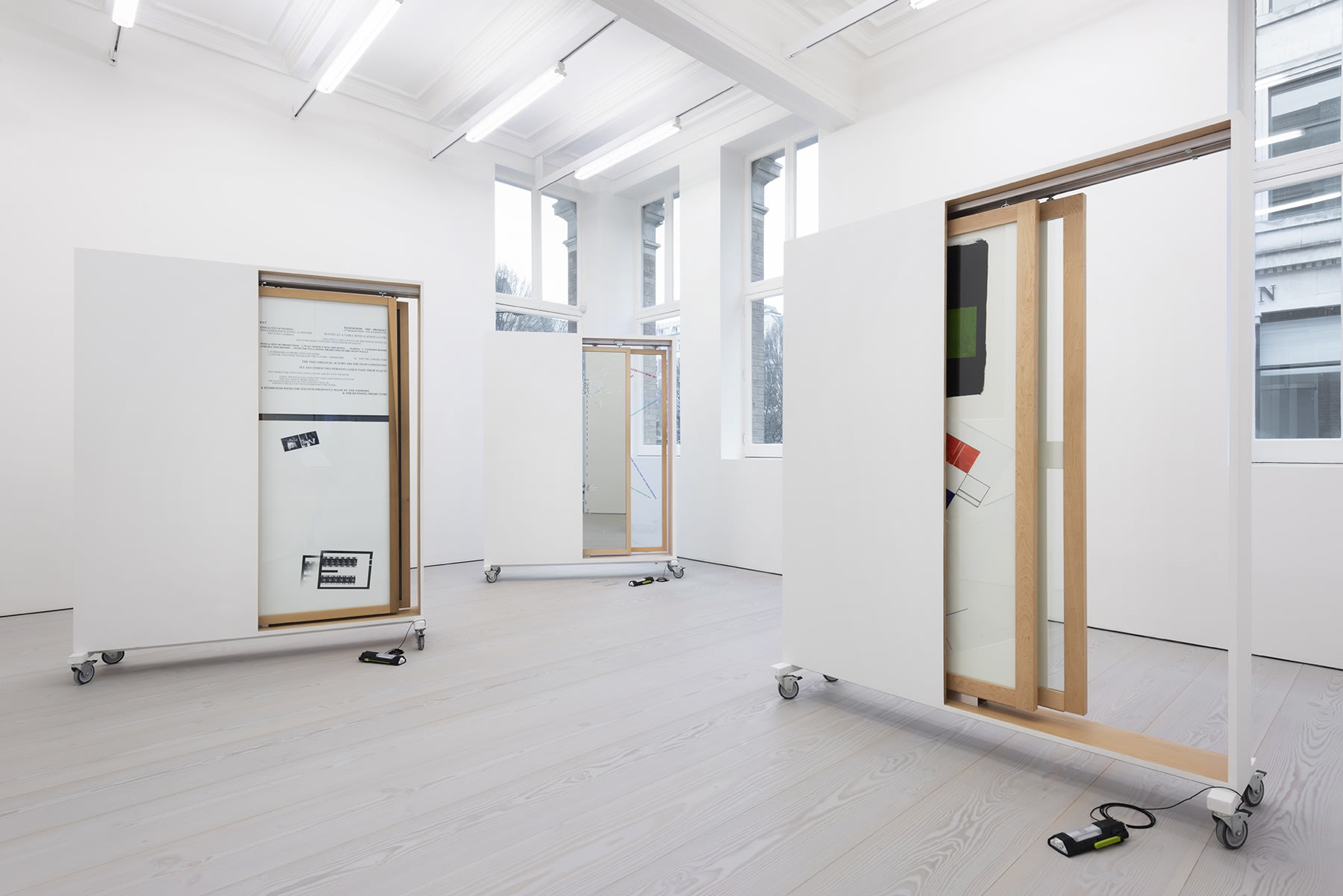 3 structures on wheels contain sliding doors displaying drawings.