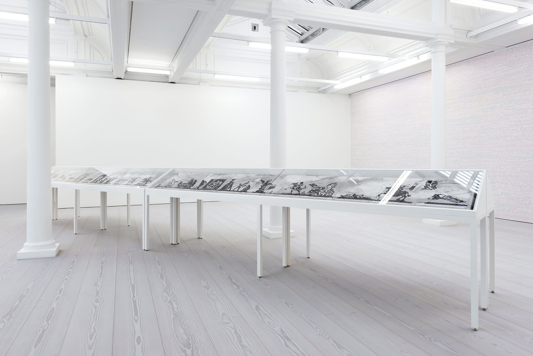 Charcoal drawings are displayed in a long vitrine in a white room with skylights.