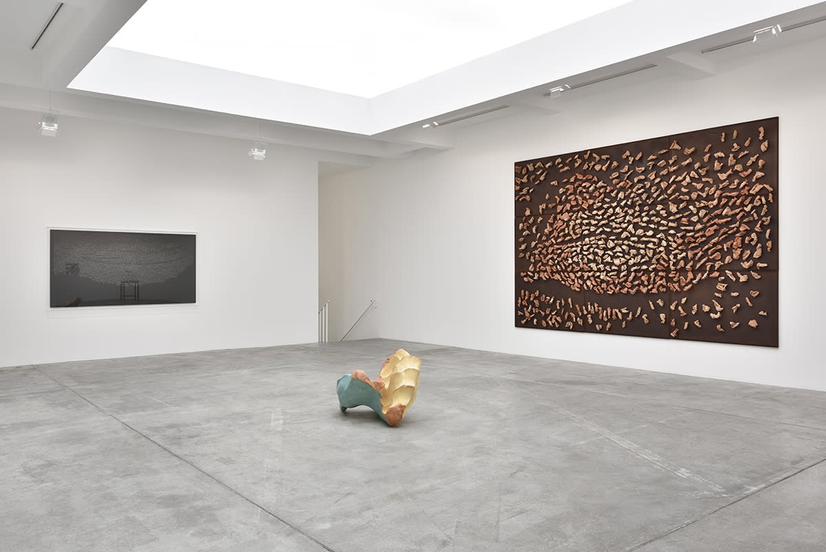 In a large white space with a skylight, a large brown canvas hangs on the right wall, covered in mounted wood objects. A wood sculpture sits on the floor in front of it, and a black painting hangs on the opposite wall.