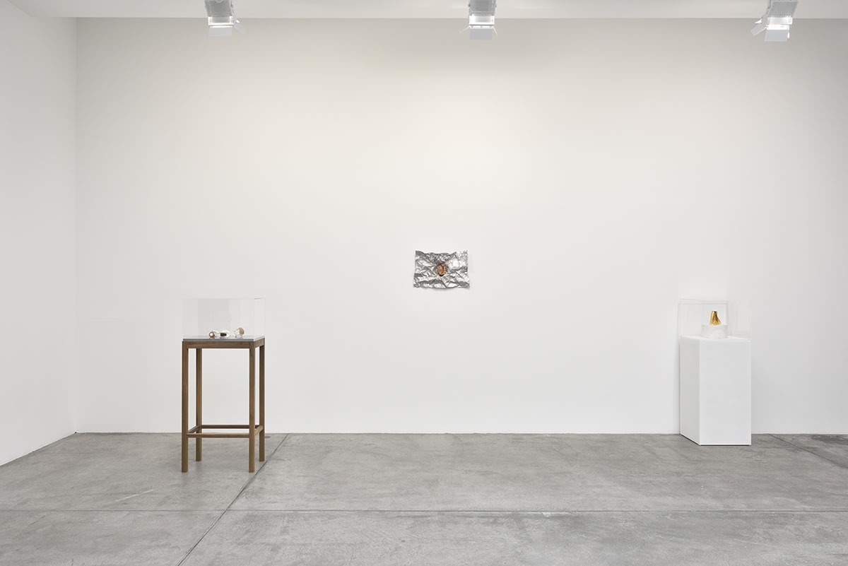Between two elevated display cases with small objects, a small abstract painting hangs on the wall. It appears to be made up of crumpled tin foil.