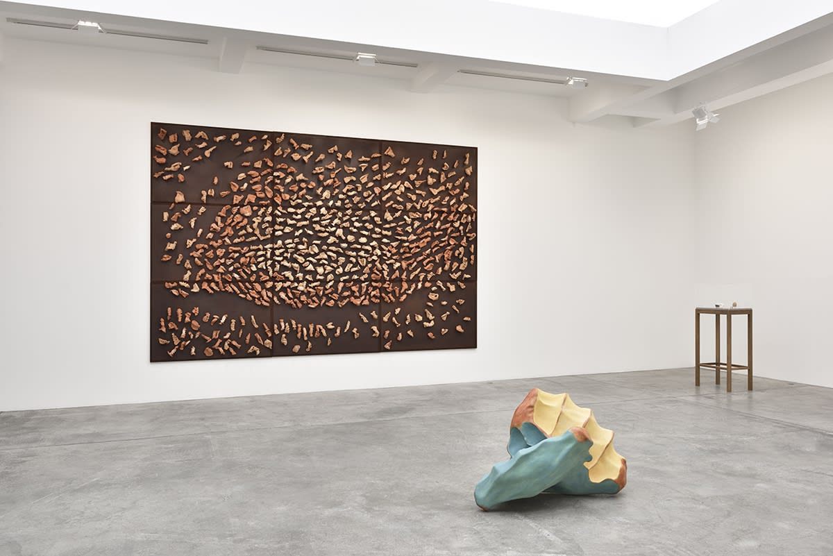 In a large white space with a skylight, a large brown canvas hangs on the wall, covered in mounted wood objects. A wood sculpture sits on the floor in front of the painting, and an elevated display case with small objects sits next to it.