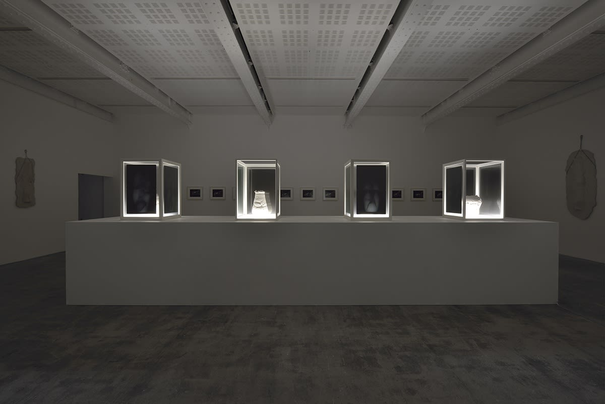 In a dark room, there are no lights except for those that illuminate, from below, white pottery in dark shaded display cases on a large white platform.