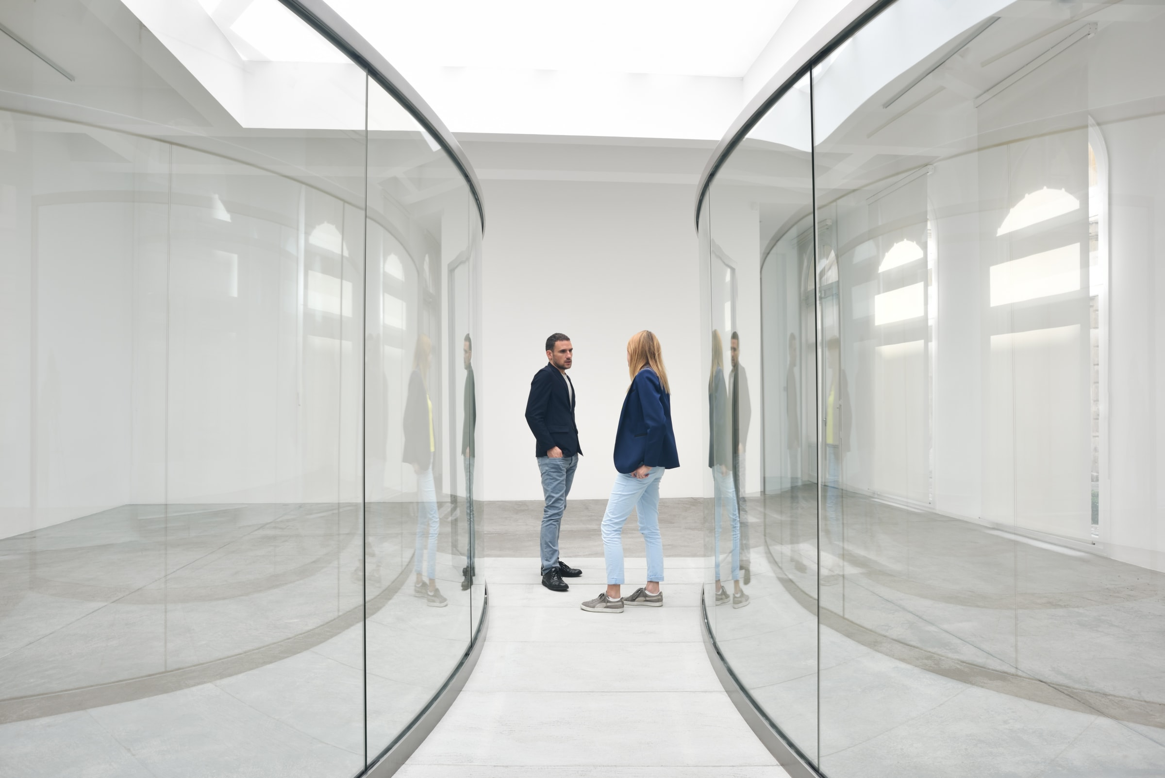 Gallery installation: two people stand in-between two curved glass walls.