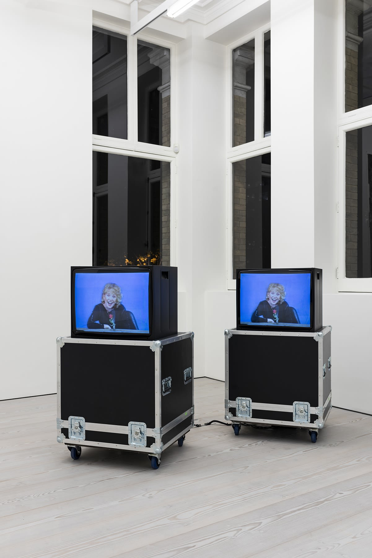2 T.V. monitors display a woman laughing, in the corner of a white room in front of windows at night.