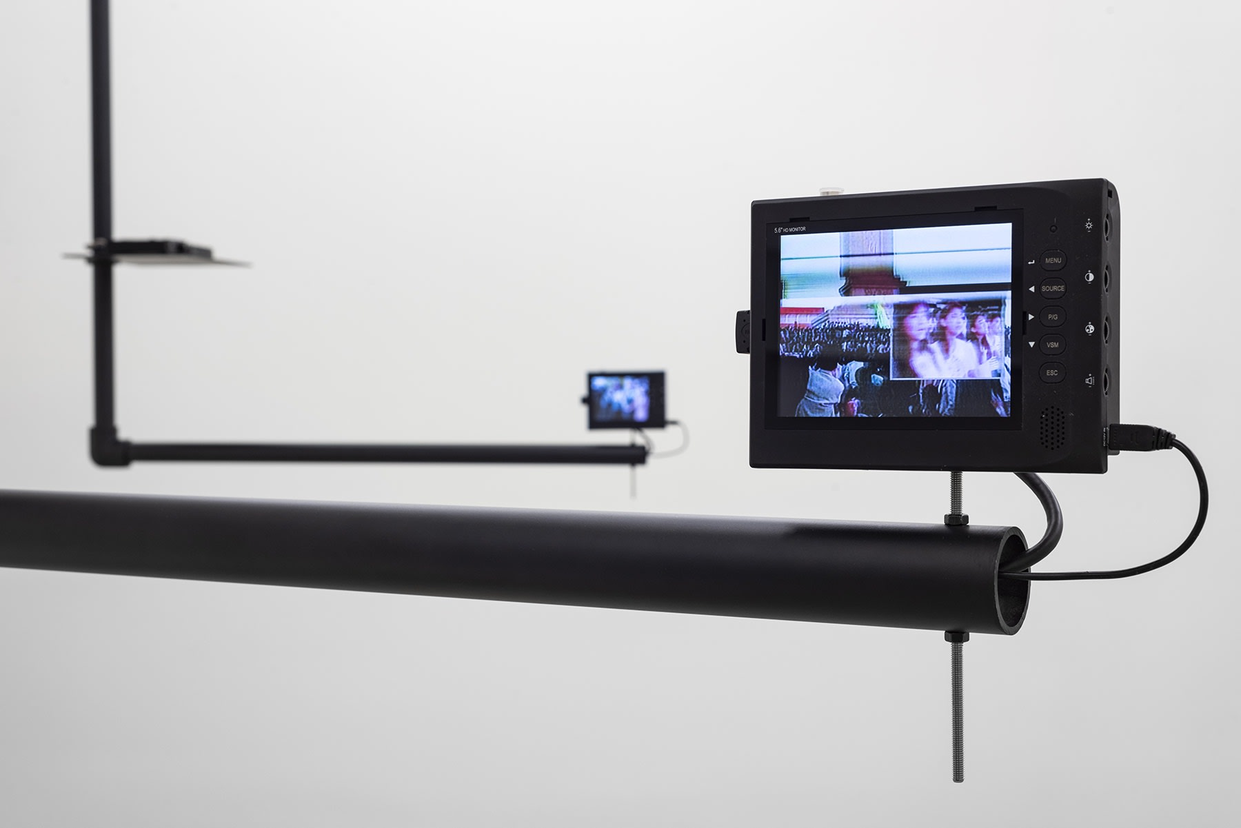 A small screen plays a video with vertical bands displaying an indistinct crowd.