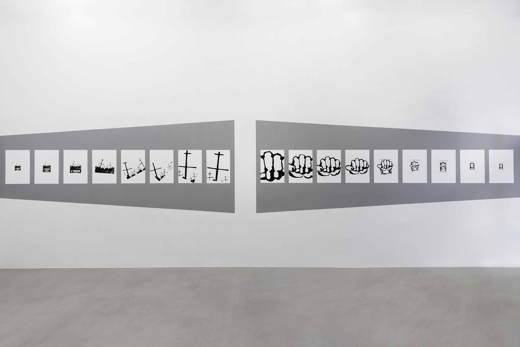 17 ink drawings on paper are displayed horizontally on a gallery wall on top of a grey quadrilateral background.