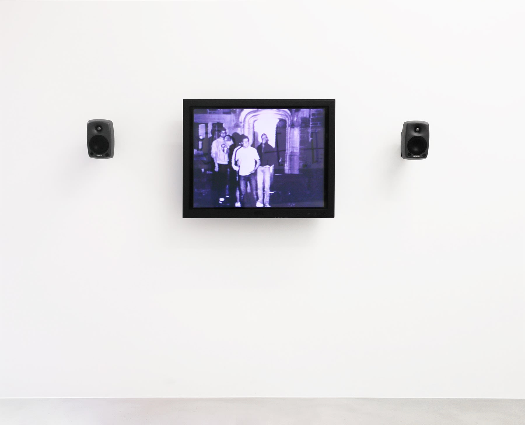 A purple monitor with 2 speakers displays an image of figures gathered outside.