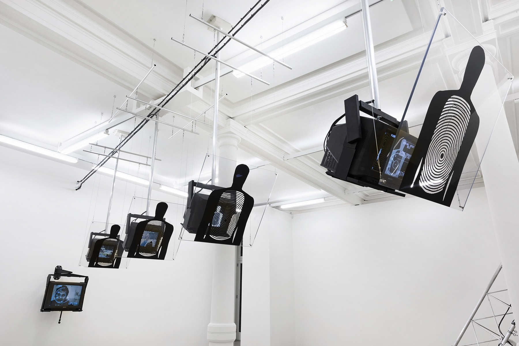 5 TVs hang from the ceiling with shooting targets shaped like the human form placed in front.