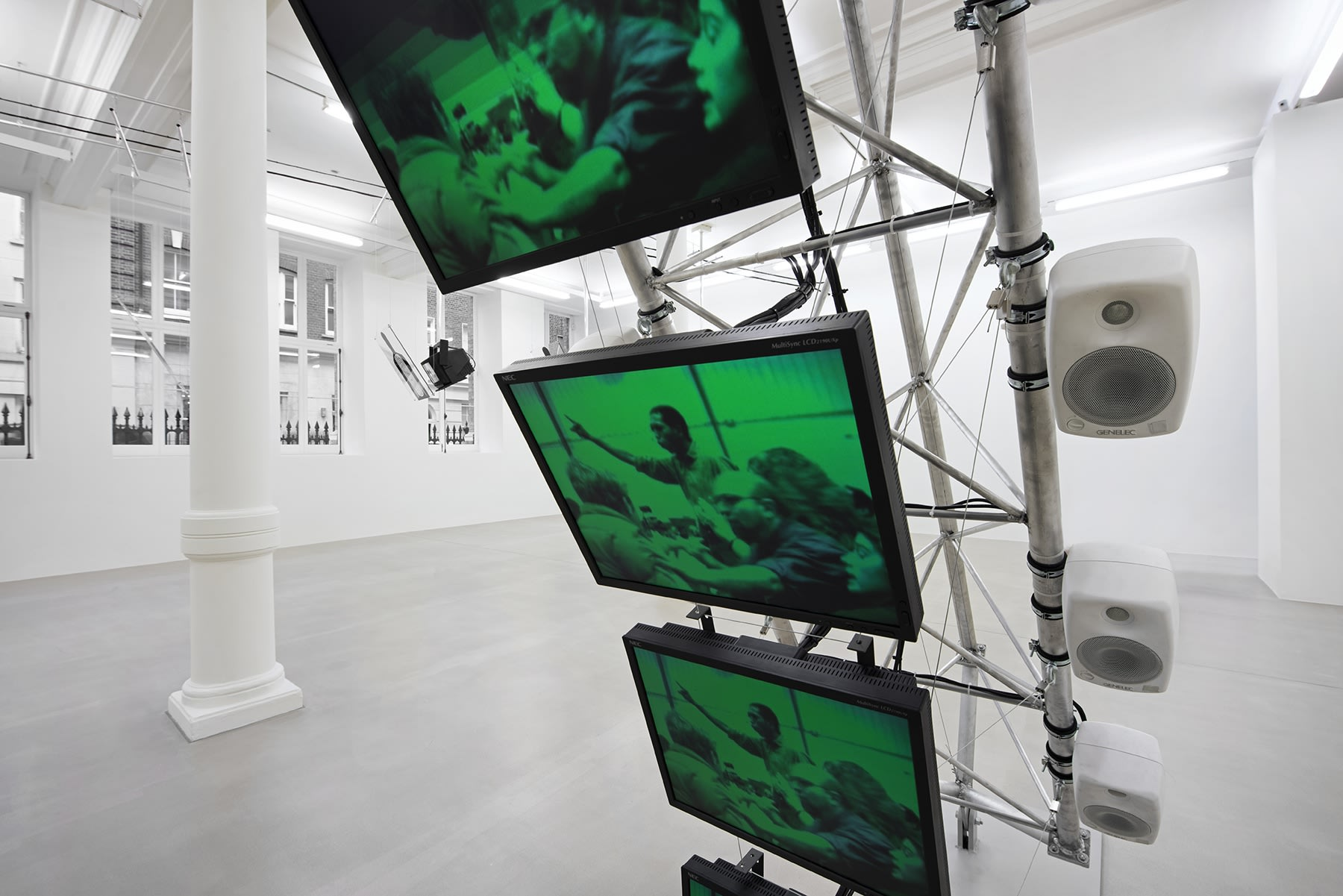 A close-up of 3 monitors stacked vertically displaying a green image of a crowd.