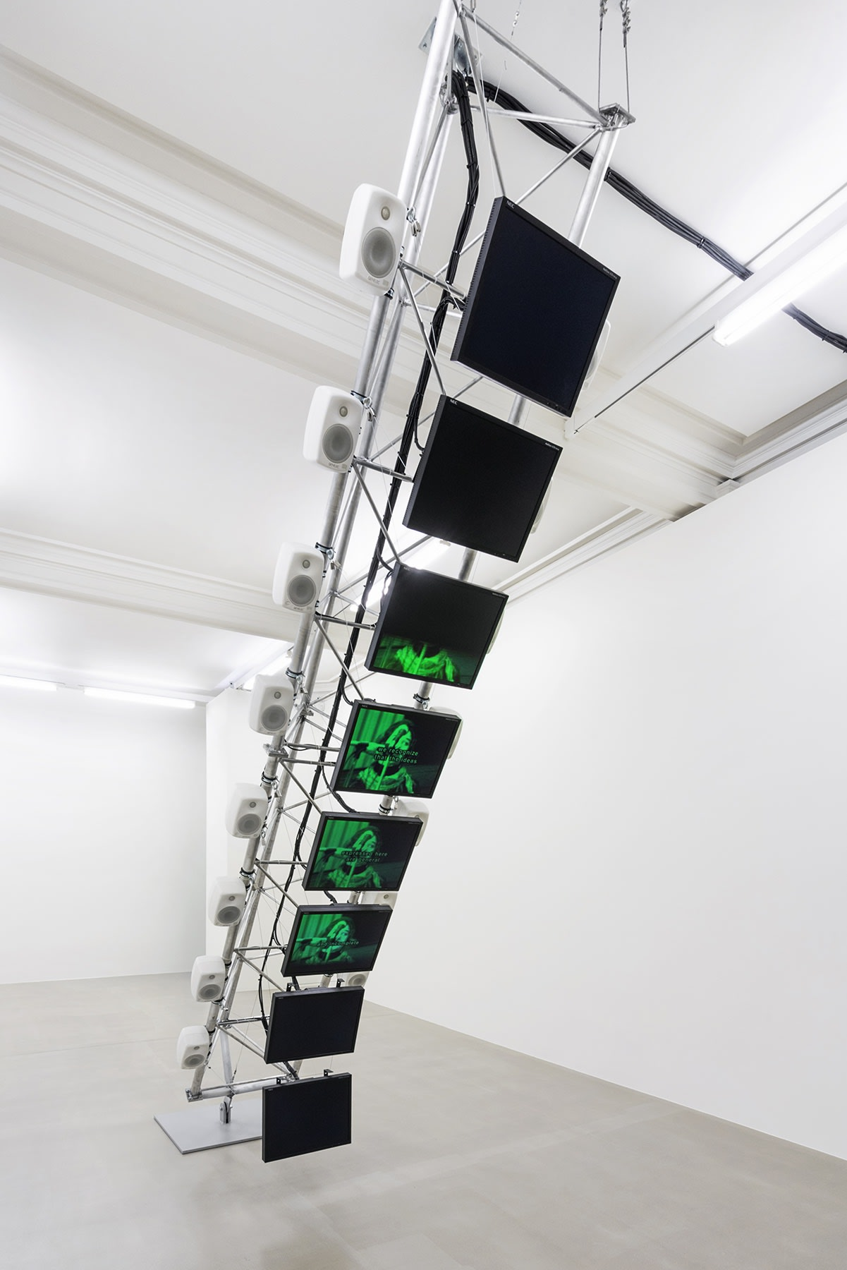 8 flatscreen monitors are displayed vertically on a metal armature in the center of a white gallery space.