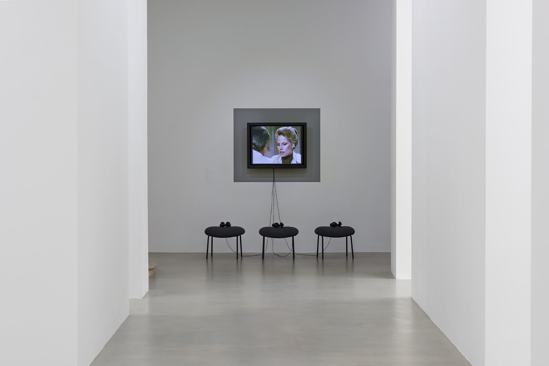 3 stools with headsets sit in front of a flatscreen monitor displaying a woman and a man conversing.