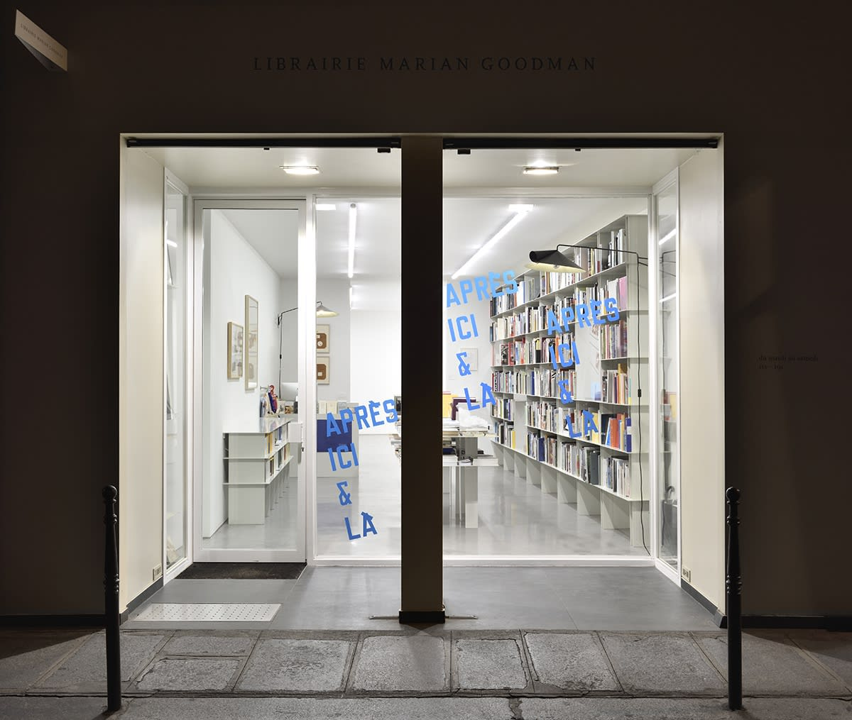 View of the librairie lit up from the interior as seen from the street at night.