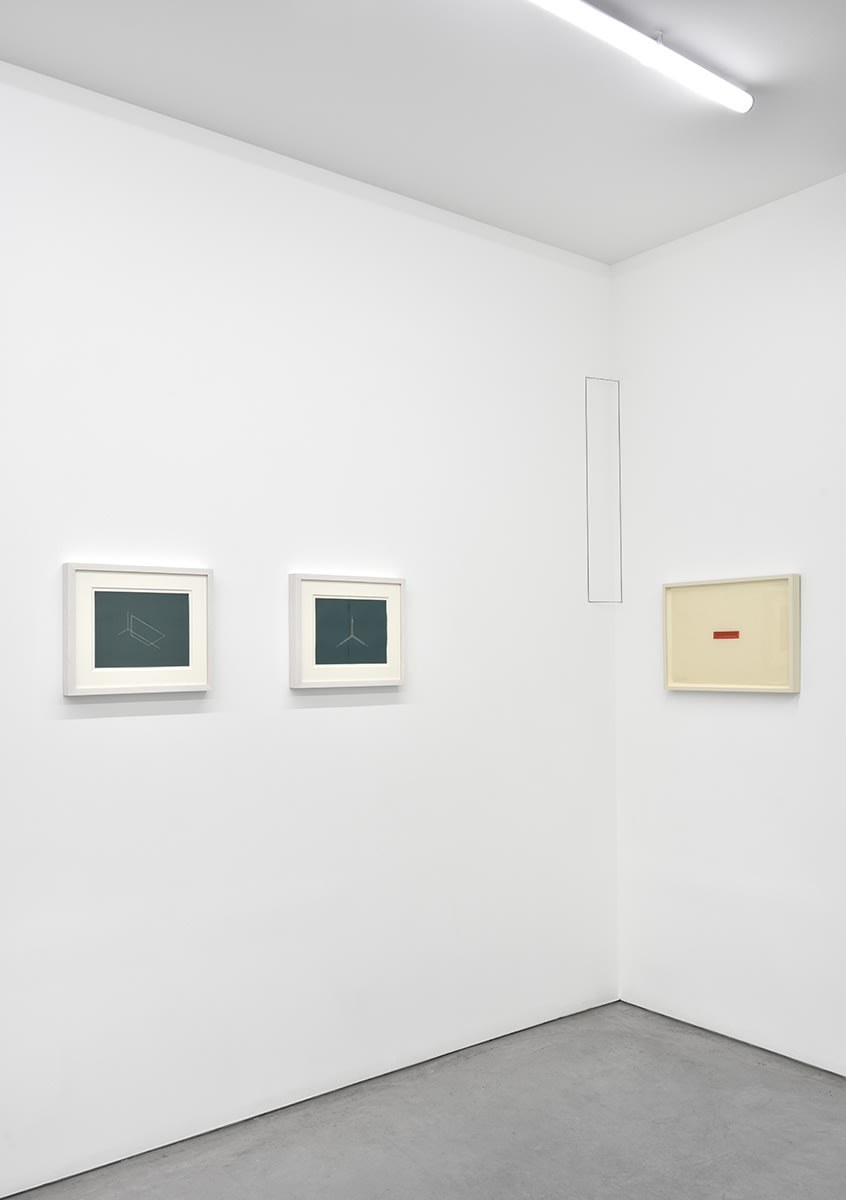 3 small, framed artworks hang in the corner of the gallery.