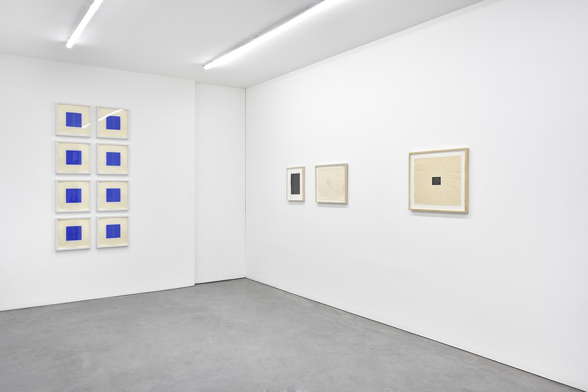 11 framed artworks hang in the gallery. To the left, they form a grid of blue squares.