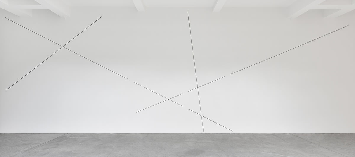 Black lines form a geometric abstract pattern on the gallery wall.