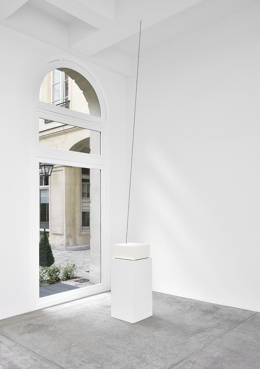 A pedestal sits in front of a window in a well lit gallery. A dark line is suspended from the ceiling.
