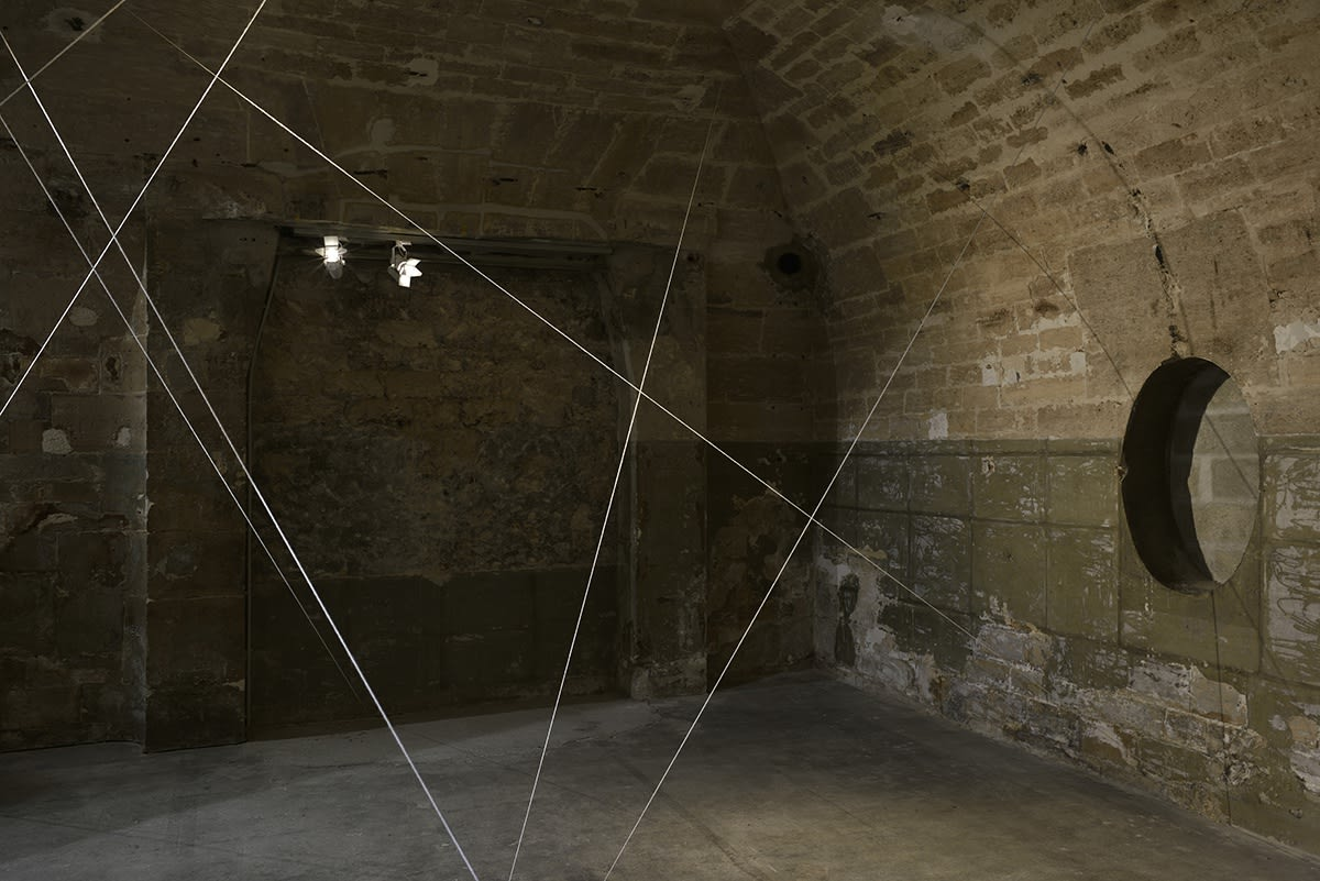 White cords are suspended in a dimly lit room with brick walls.