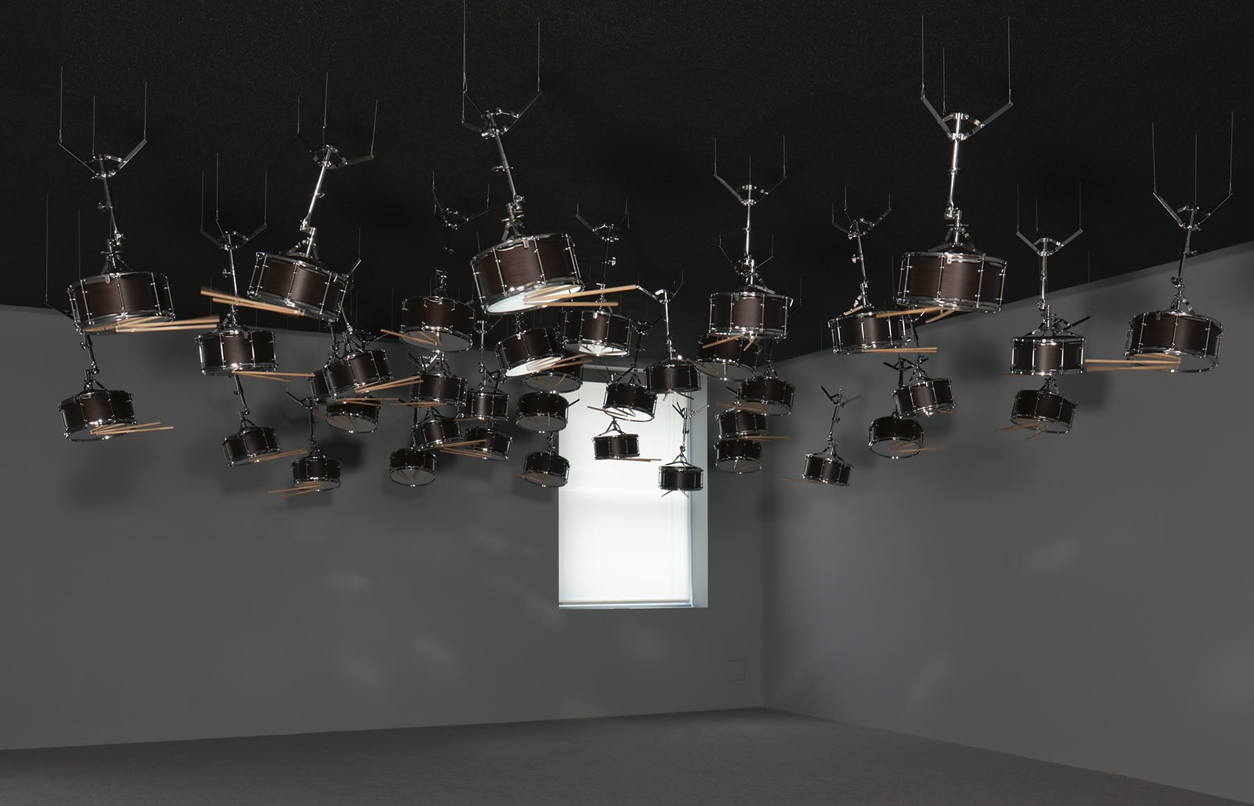 Snare drums suspended upside down from the ceiling in a grey room.