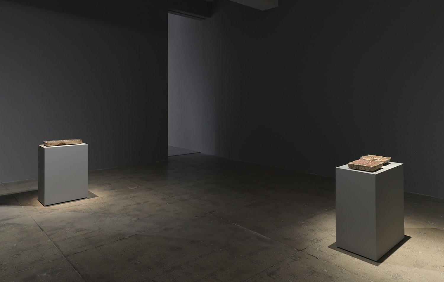 2 grey pedestals spotlit in a grey room displaying flat objects.