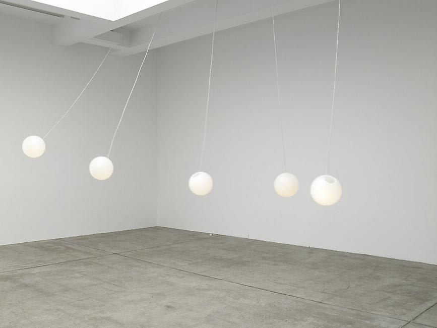 5 white balls hang from the ceiling in a white room.