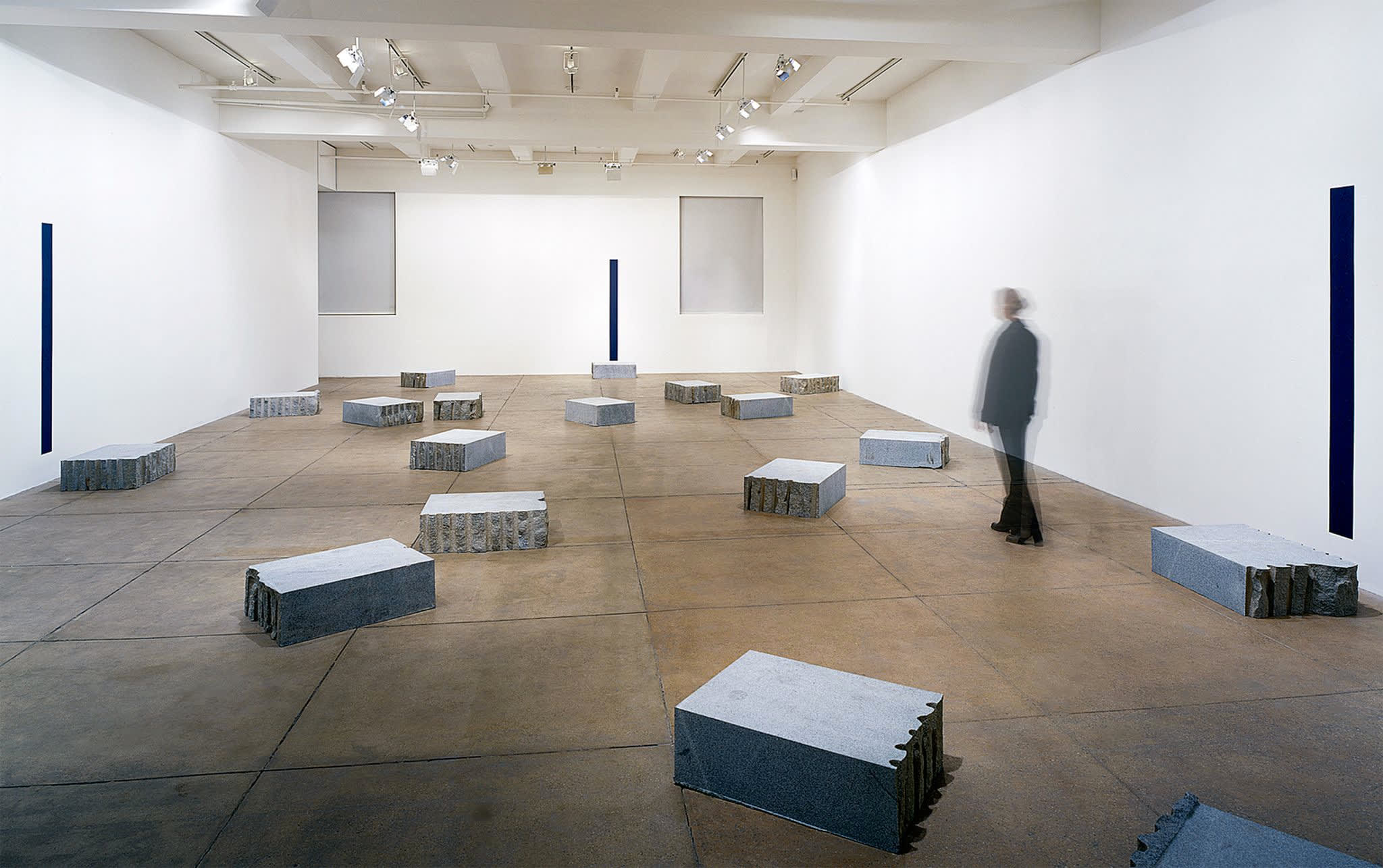 Multiple concrete slabs lay on the floor, a motion blurred figure walks among them.