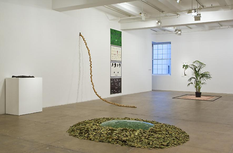 An installation view of various sculptures made of plants and leaves and artworks on a white wall.