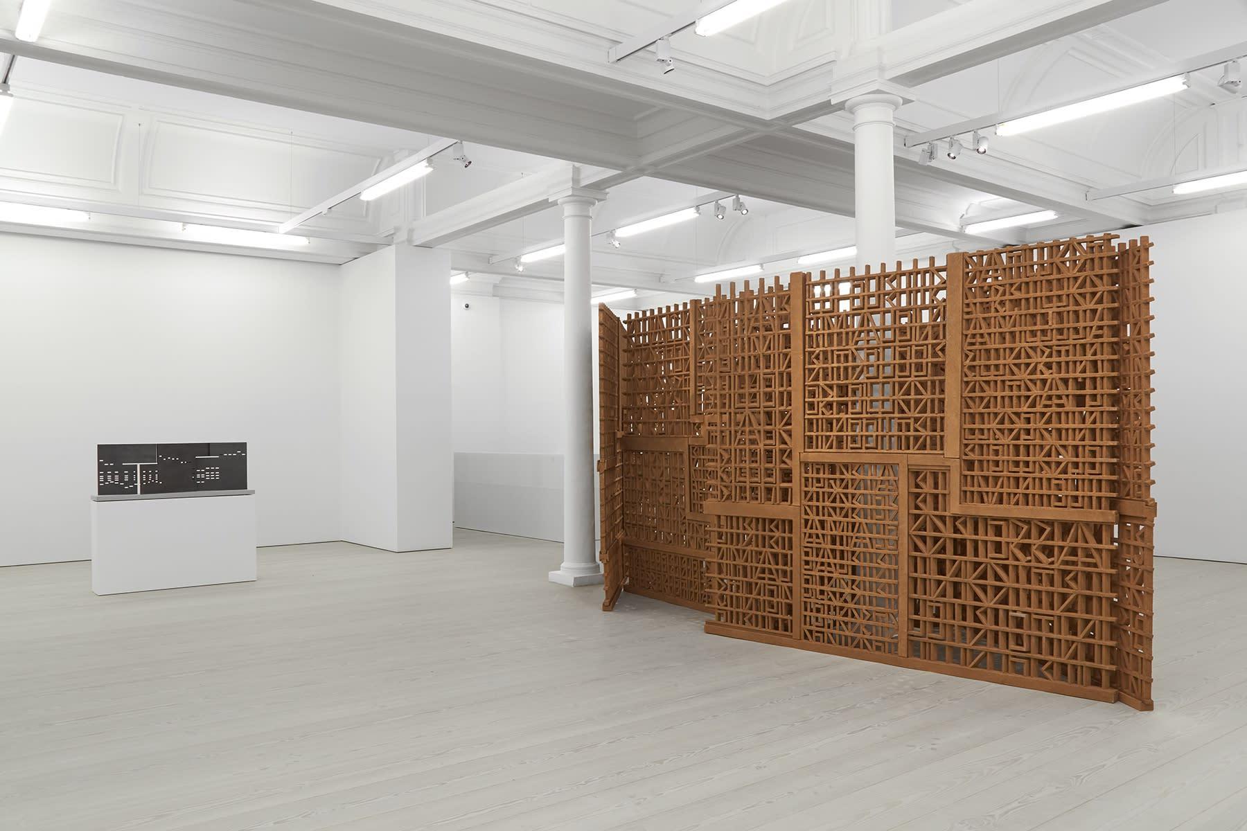 A Cristina Iglesias artwork spans the middle of the room around 2 white columns.