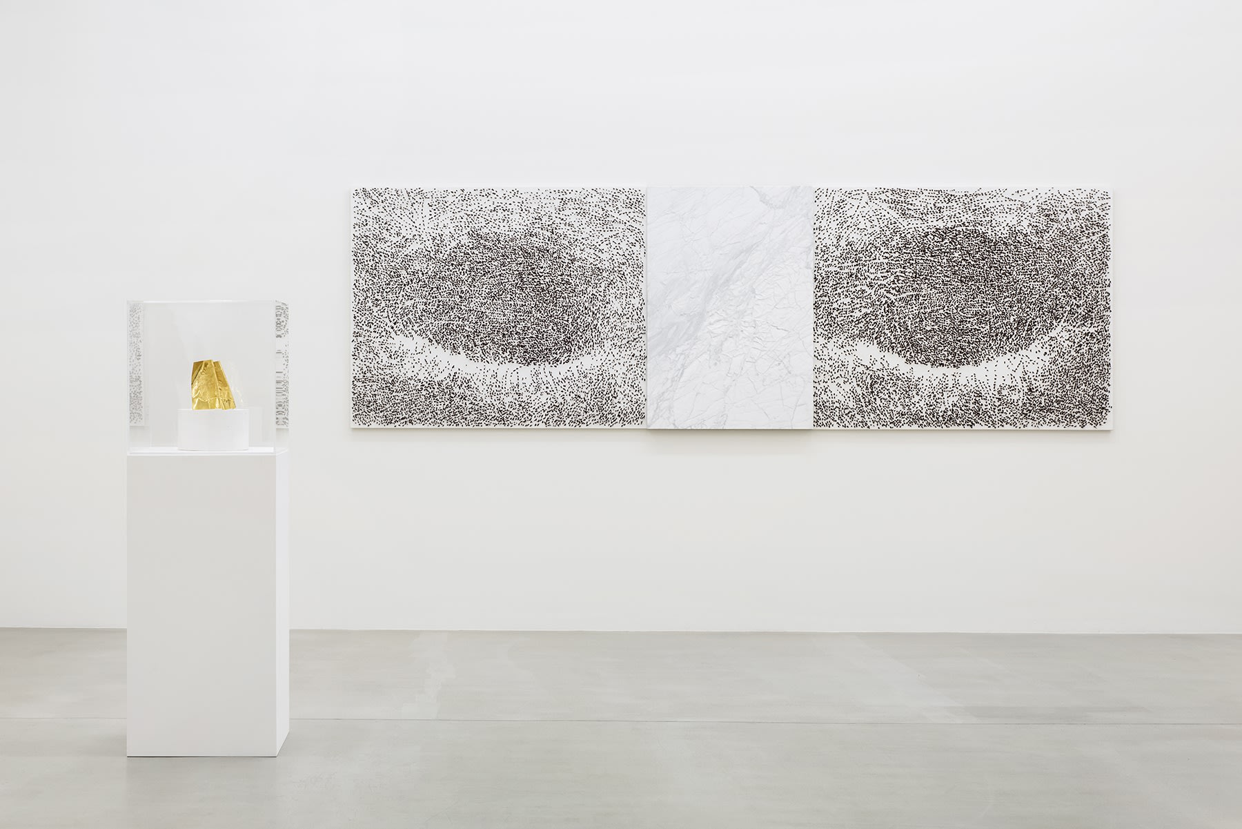 A gold object on a pedestal stands in front of a black and white abstract drawing on a gallery wall.