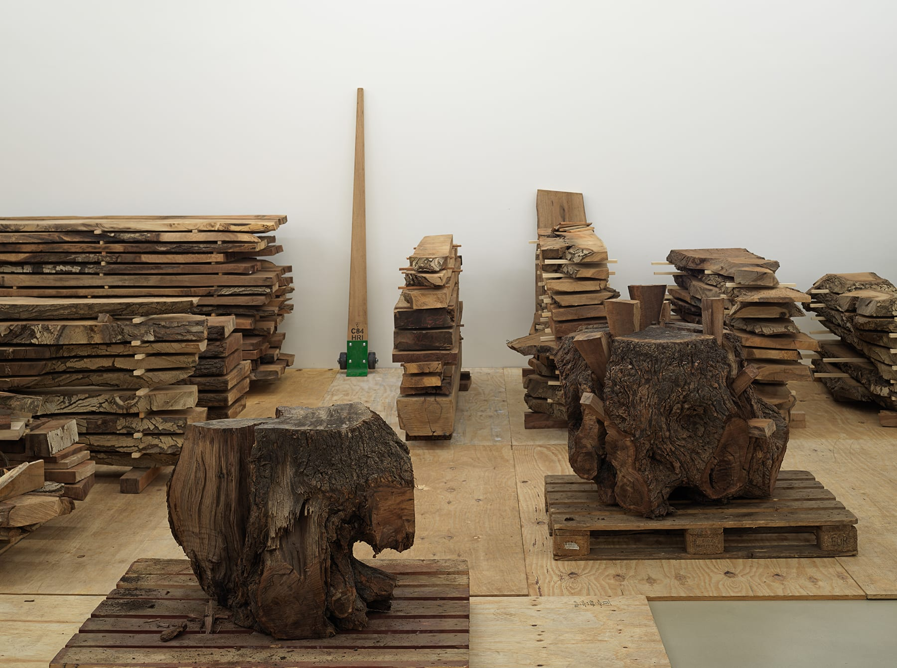 Gallery filled with stacked wood on crates and plywood