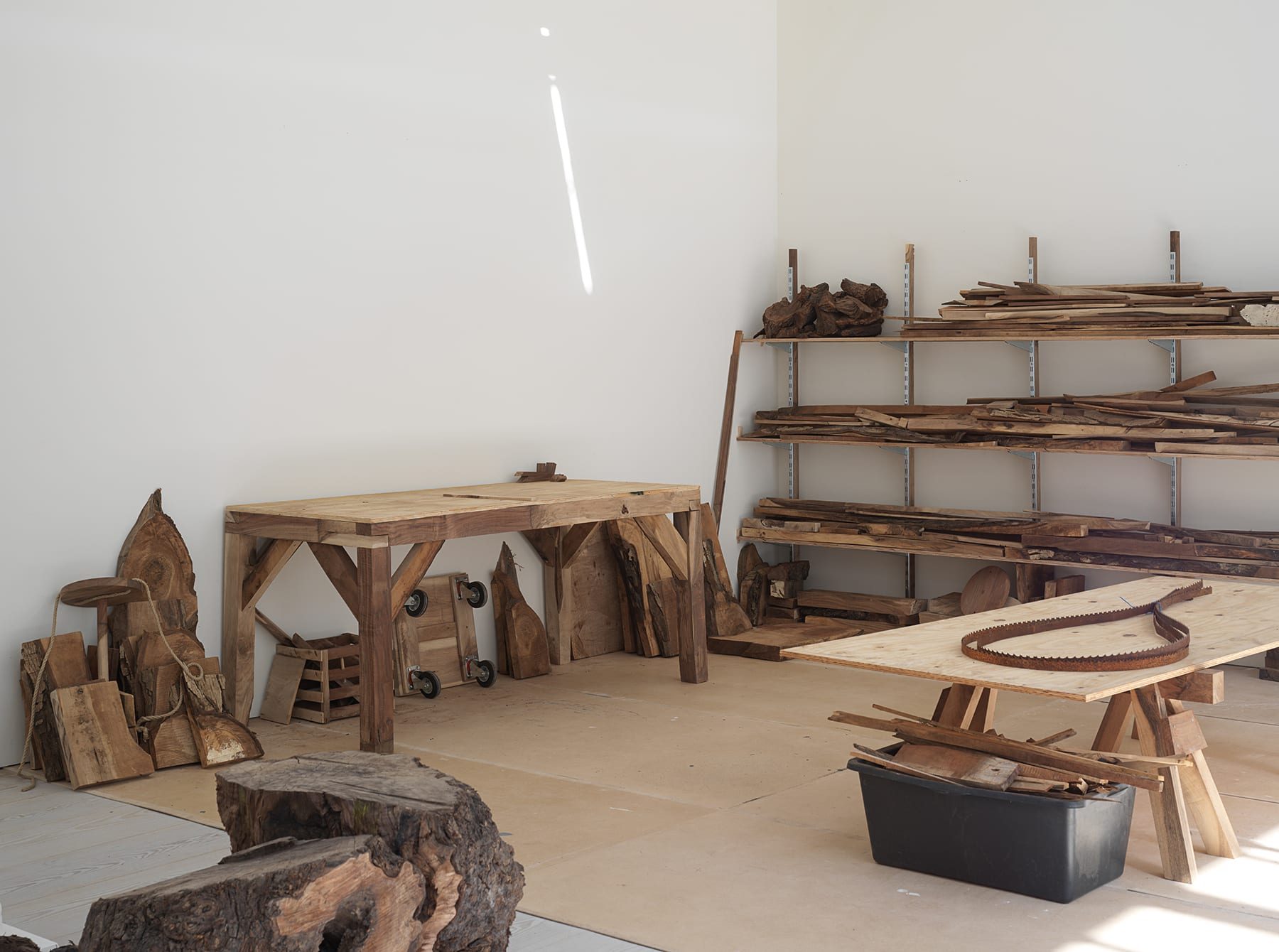 Gallery filled with a couple of working tables and wood stored on shelves, in bins and along gallery wall.