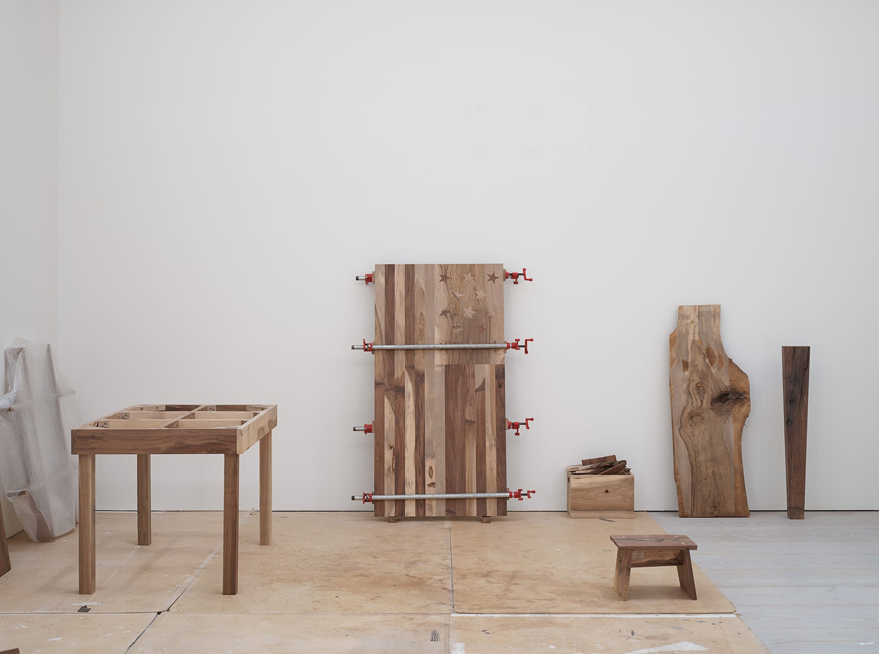 Gallery filled with various wooden furniture, wooden slabs, and a clamped wooden flag sculpture.
