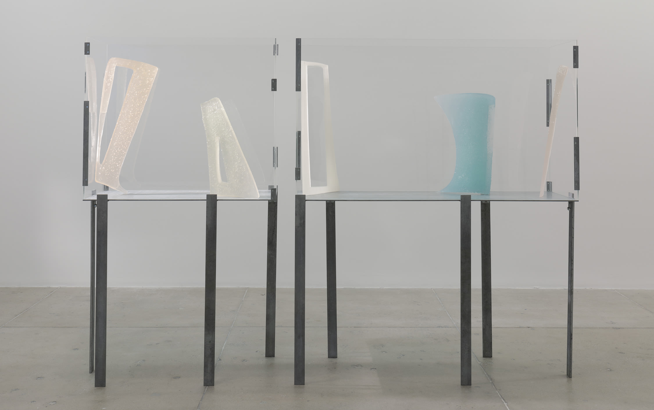 Pastel colored abstract sculptures stand encased in glass on a metal table.