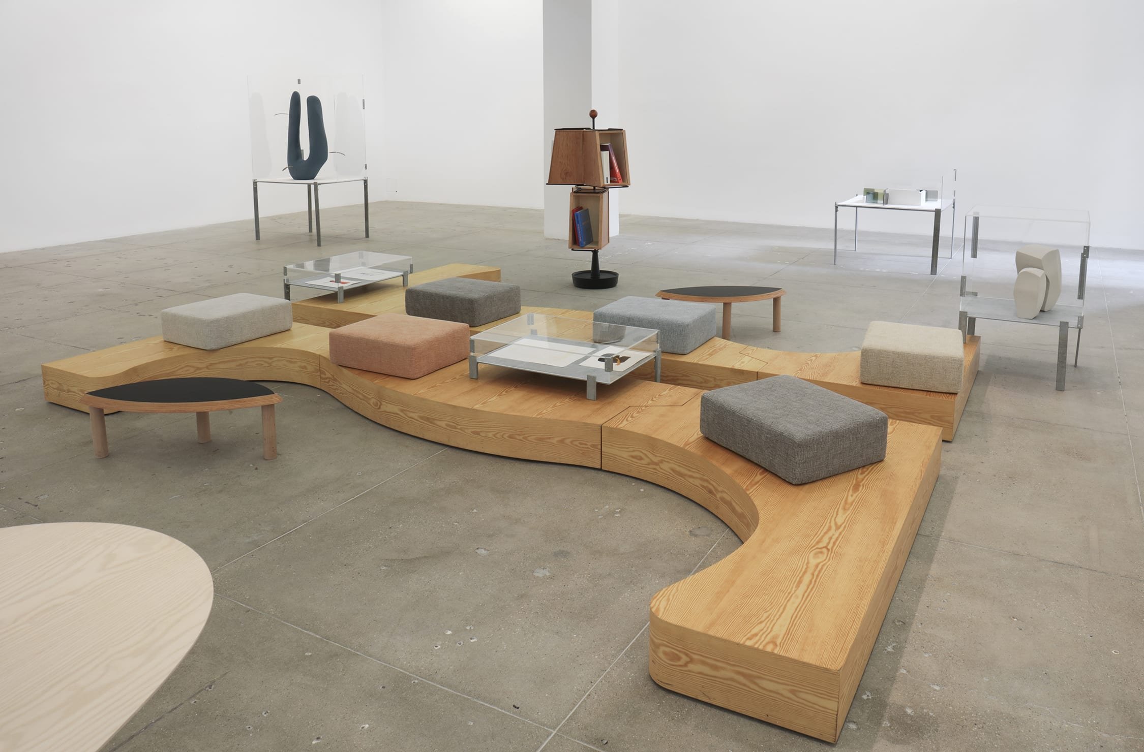 An installation view of sculptures, custom furniture and cushions in a white gallery space.