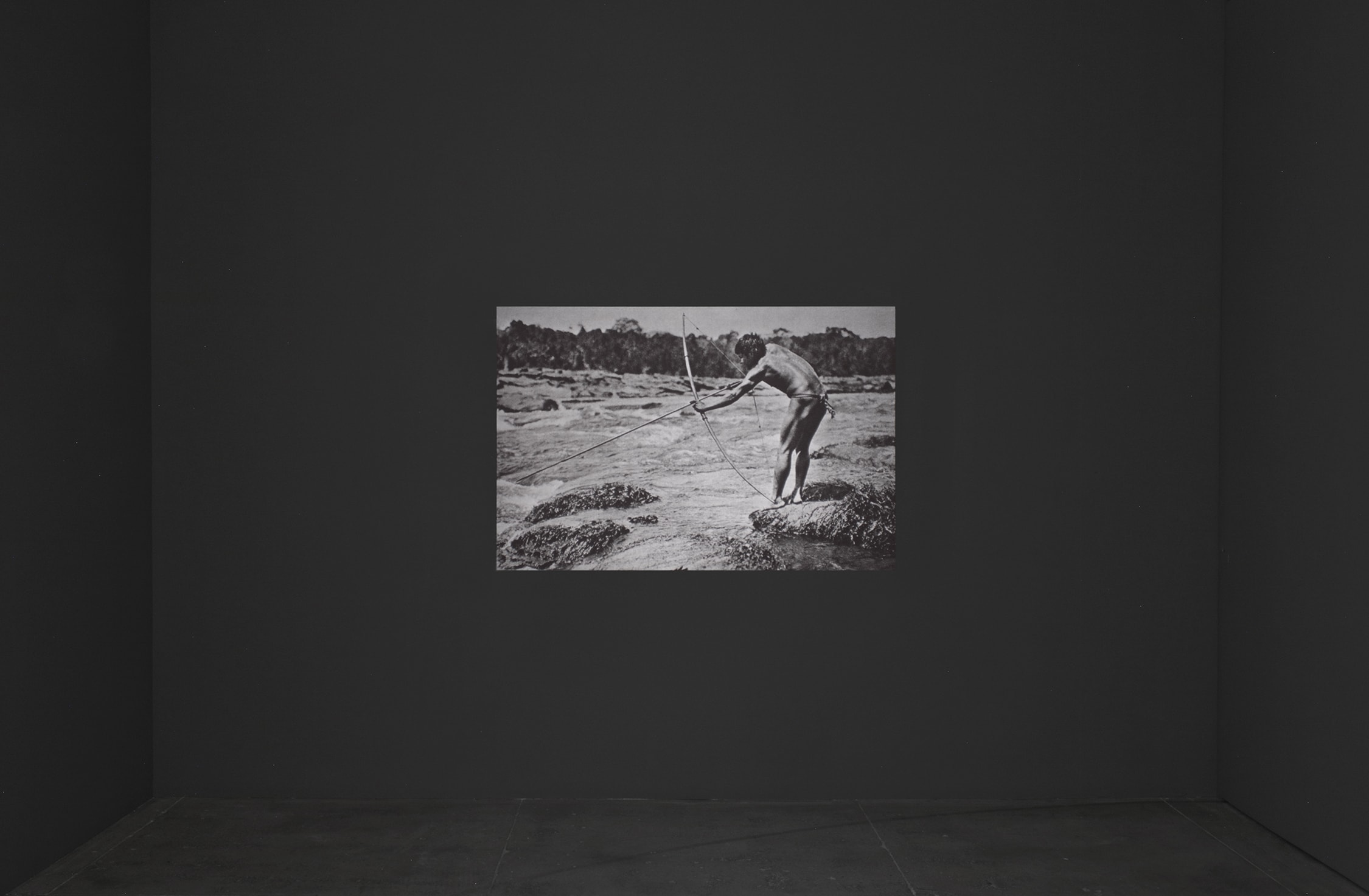 Installation view of Lothar Baumgarten's film. A black-and-white shot, containing a man, a bow and arrow, and a body of water.