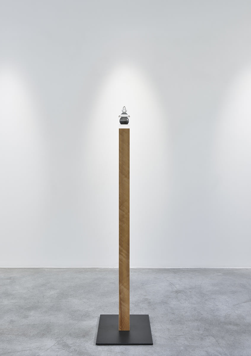 Gallery installation: singular wooden plank vertically placed with a small glass orb sculpture resting on top.