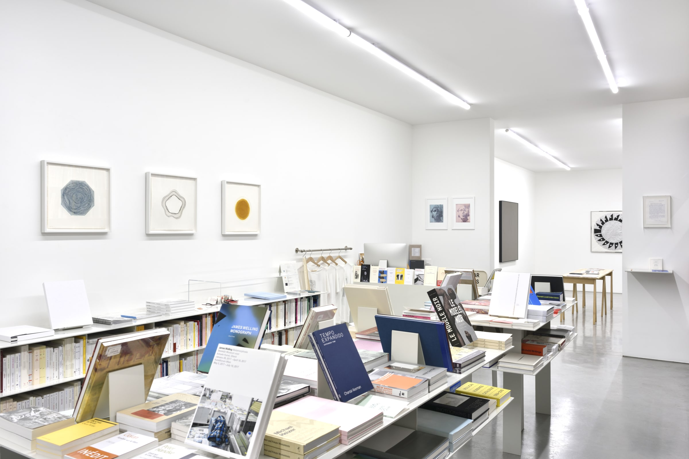 Various framed artworks on brightly lit, white walls. There are shelves displaying books in the center and along the wall.