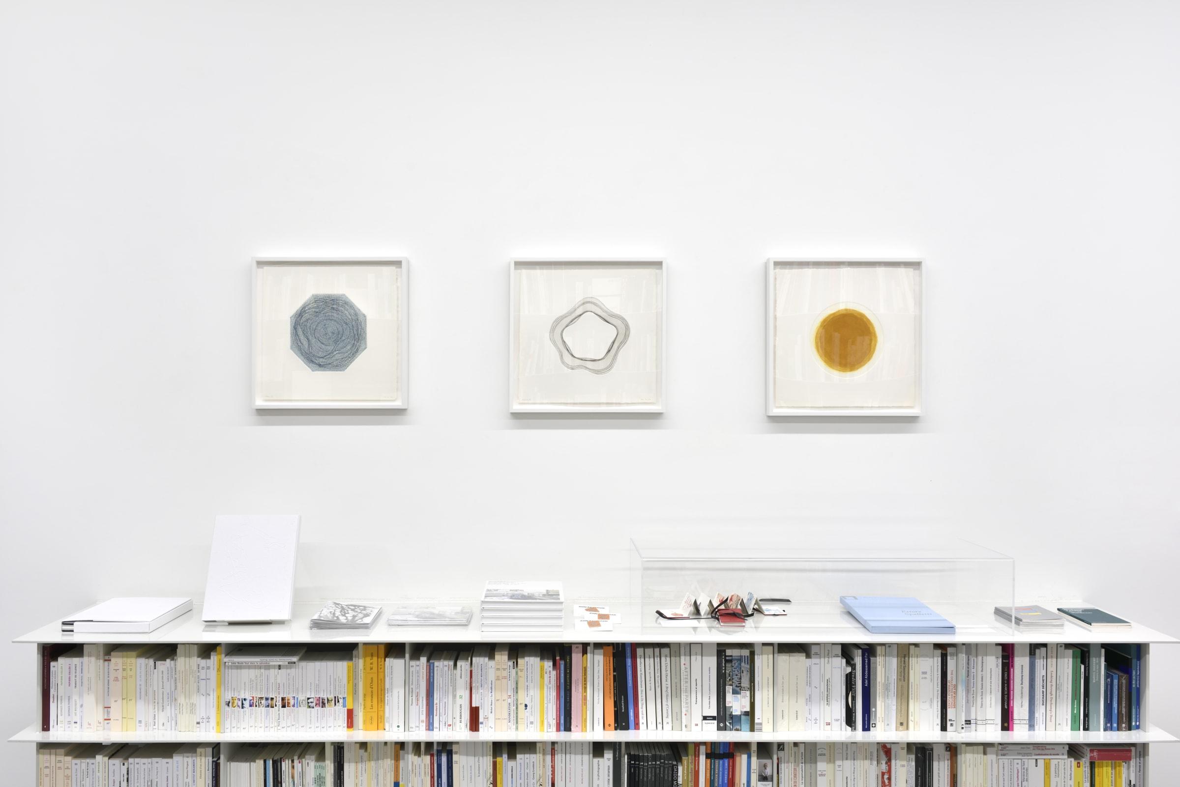 3 framed prints hanging on a white wall over bookshelves.