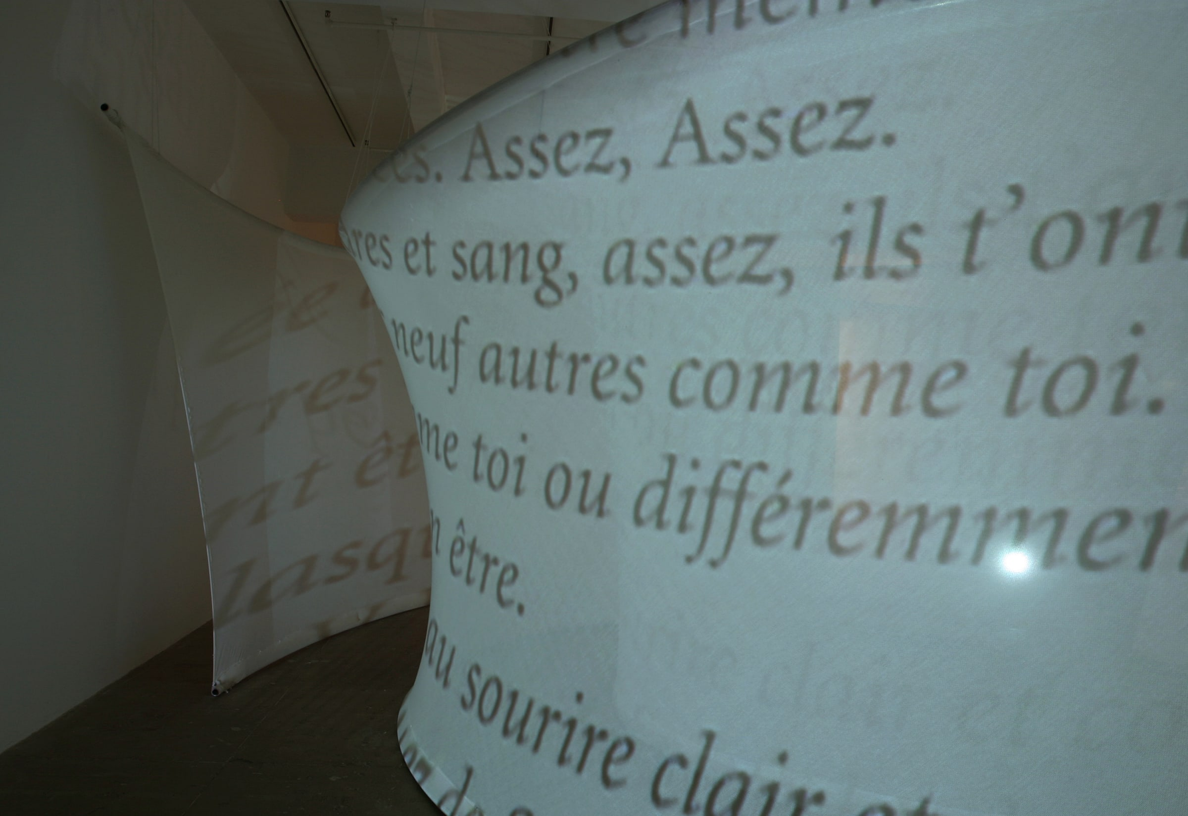 Text in french projected onto a curved, white, translucent piece of fabric stretched from floor to ceiling.