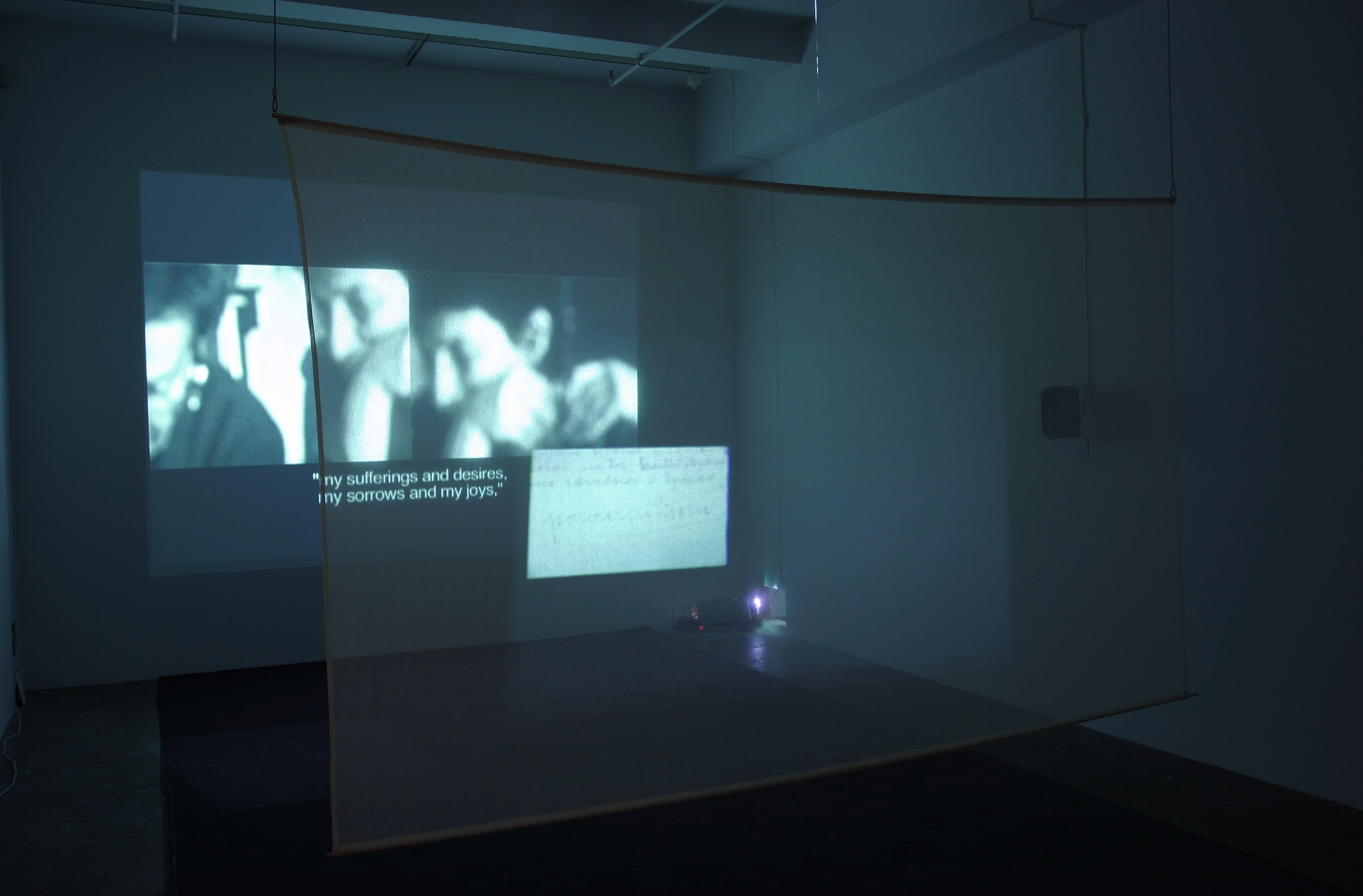 An image of 2 people with subtitles is projected through a transparent piece of fabric onto the wall.