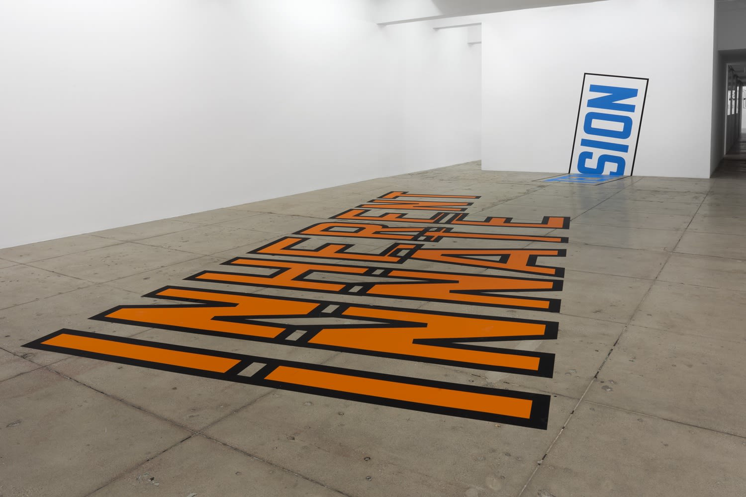 "Orange text with black outline on gallery floor reading ""INHERENT INMATE"""
