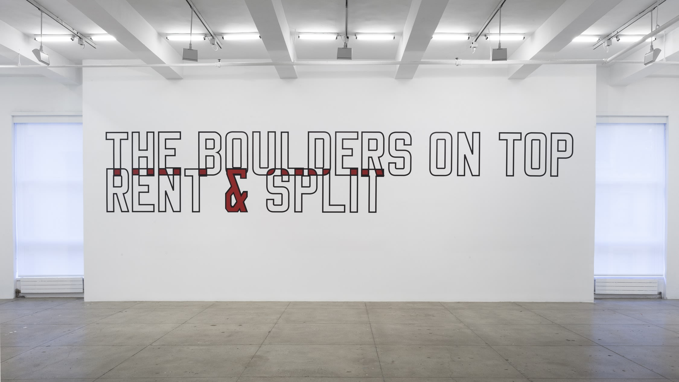 "Black outline text on gallery wall reading ""THE BOULDERS ON TOP RENT AND SPLIT IT"""