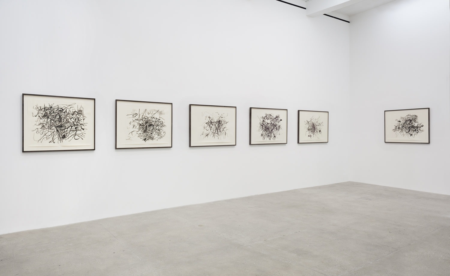 6 framed black and white abstract drawings hang on white gallery walls.