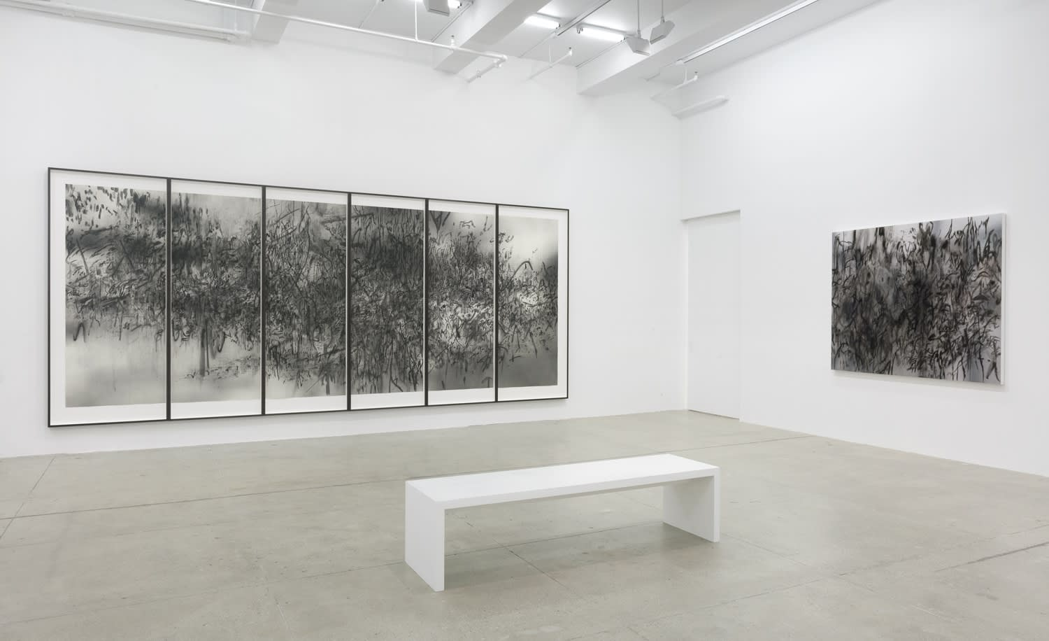 Black and white abstract drawings hang in multiple frames in a white gallery with a bench.