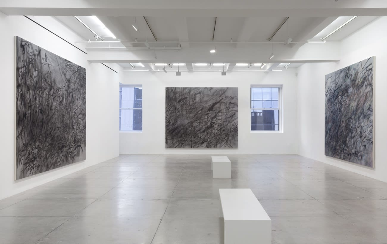 3 abstract paintings hang in a white gallery space with 2 windows and 2 benches.